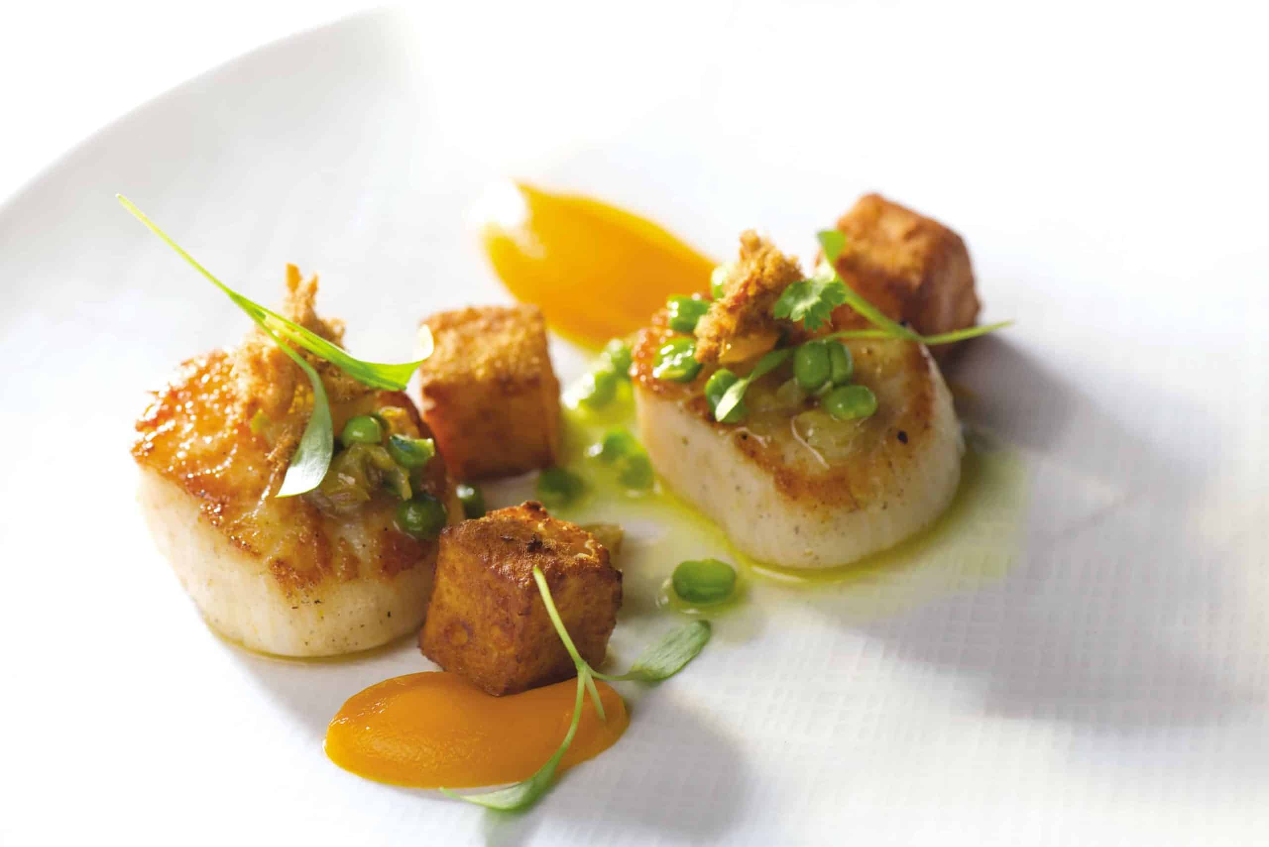 A closeup of seared scallops upon a plate at Magdalena Restaurant. This dining experience is located within The Ivy Baltimore