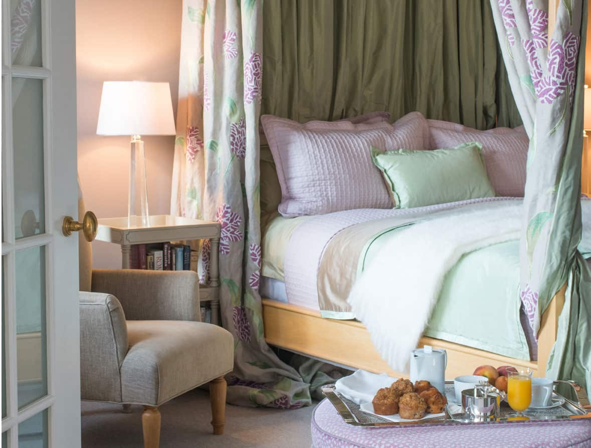 Perspective shot from the left side of the king sized bed. This four poster bed is dressed in pink and light green pastels, with matching drapes that can be drawn for extra privacy. In front, a serving tray of breakfast is set upon the Ottoman.