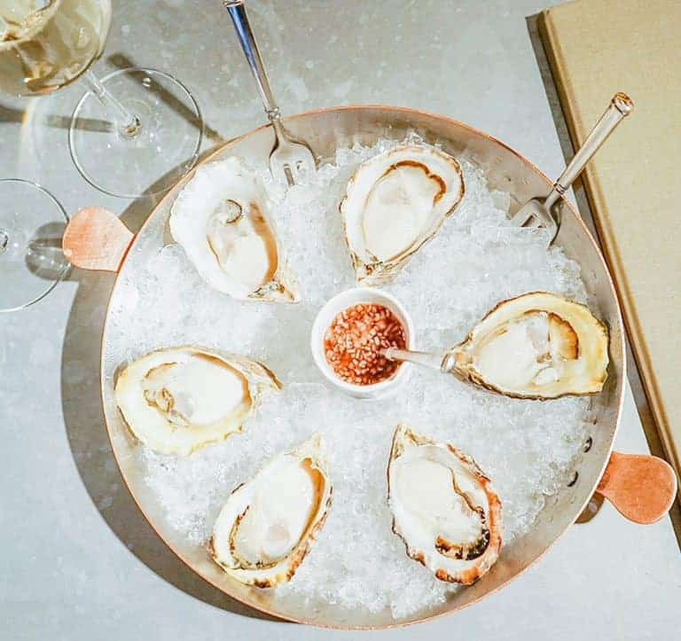 Iced plate of 6 raw oysters, with a mignonette sauce within. Two filled wine glasses and a closed Magdalena menu rest at the sides of it.