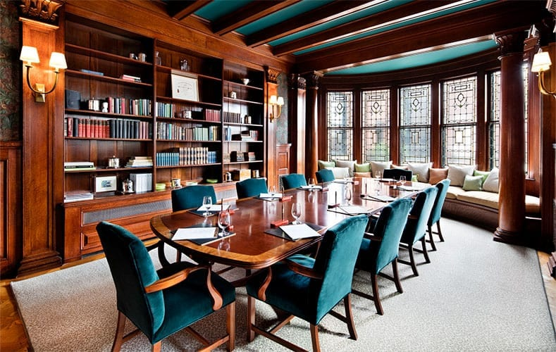 Conference room inside the Ivy Baltimore. Warm wood finish makes up the decor here, with green chairs centered around the long table. A cushioned couch is built into the window looking out.