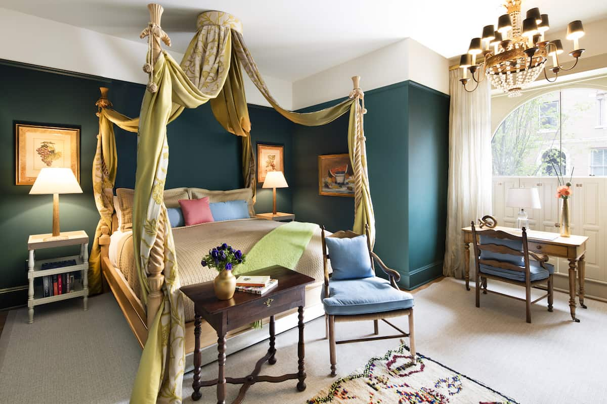 Bedroom of Suite One in The Ivy Hotel Baltimore. The four poster king sized bed offers comfort, with a chair placed just beside it. A wooden desk is placed near the window, dressed in white curtains.