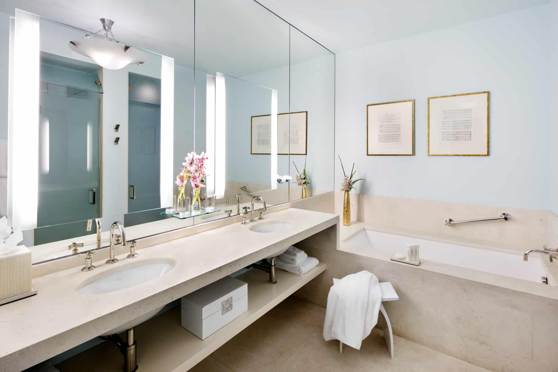 Wide Shot of a bathroom inside an Ivy Baltimore accommodation. By the bathtub, a towel is laid over a simple footstool.