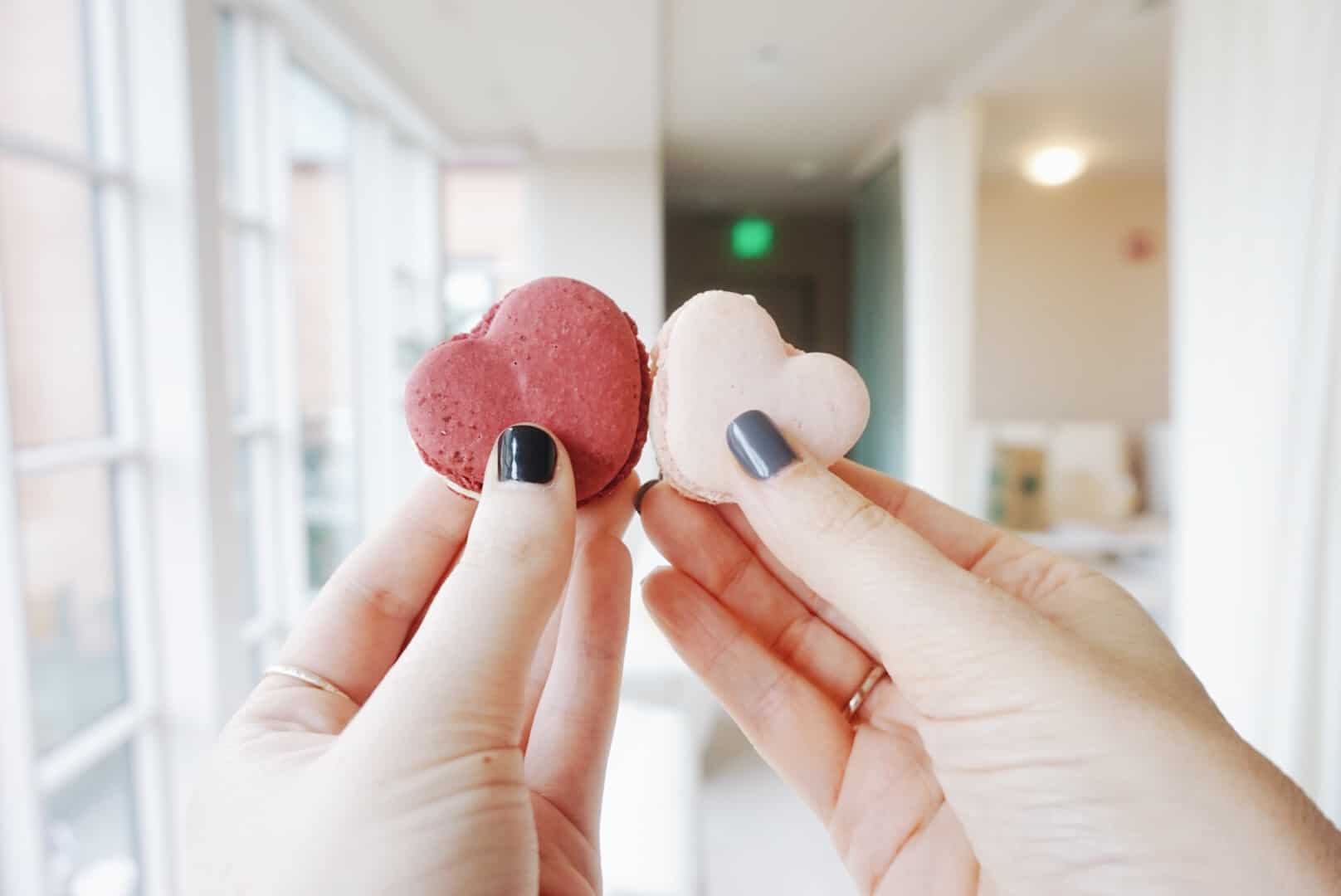 Closeup of two heart cookies held by a guest.