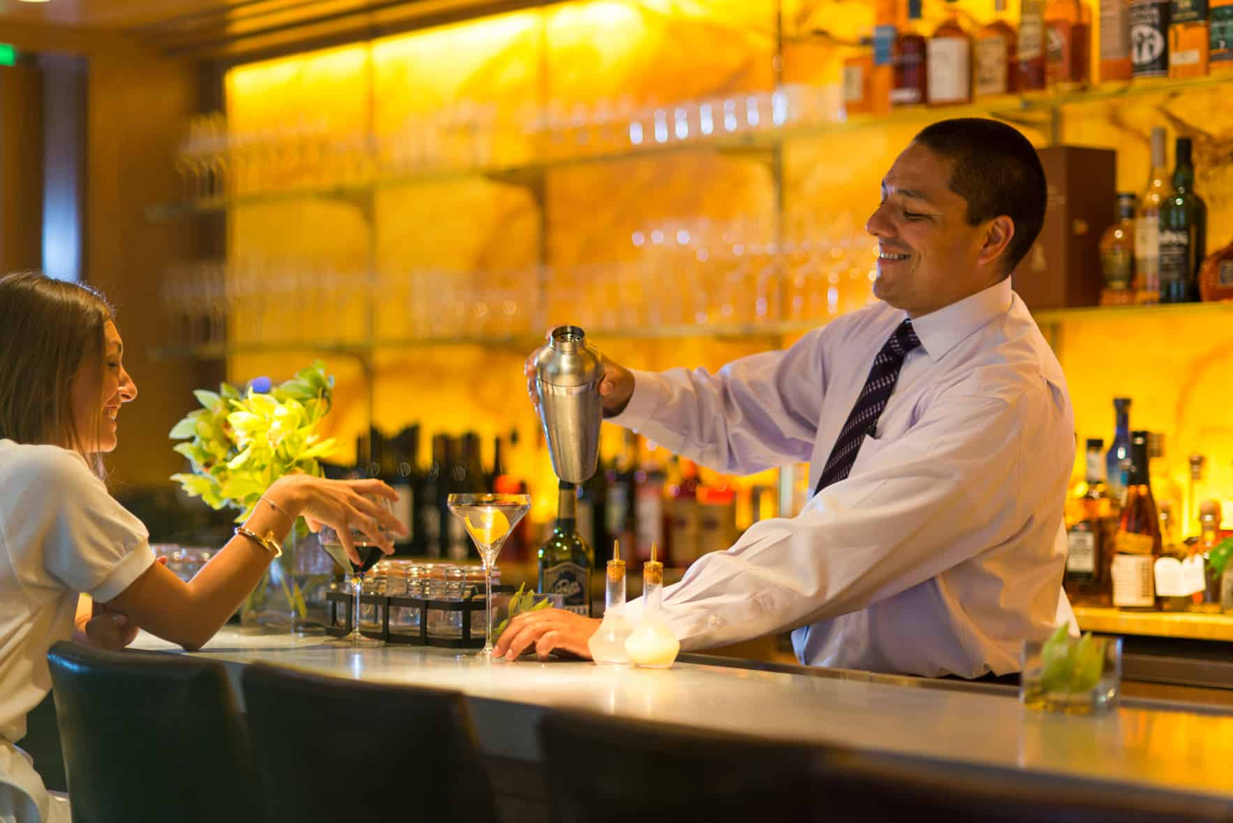 A bartender smiling as he mixes up a drink inside the bar of The Ivy Baltimore.