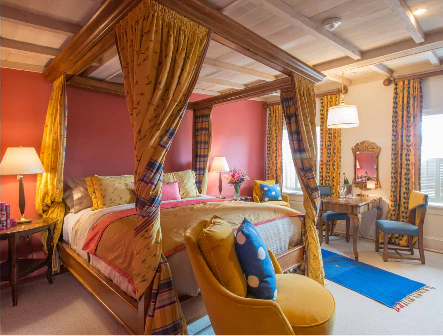 Front perspective view of the four poster bed inside the Ivy Hotel Baltimore. The bedroom goes for a storybook theme, with golds and a pattern for the canopy drapes. A contrasting blue pillow rests on the chair in front