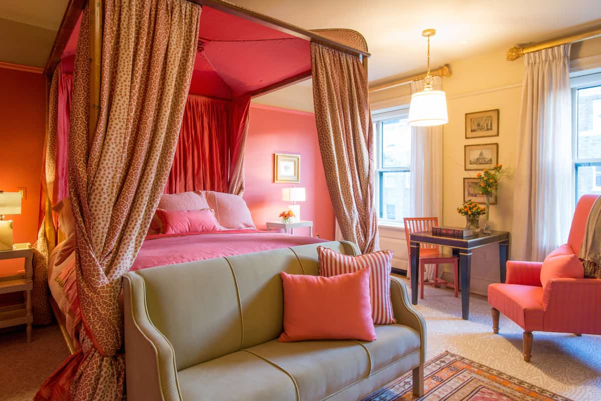 Bedroom of Room Ten in the Ivy Hotel Baltimore. Dressed in pinks and reds, the four poster king sized bed offers comfort. A couch has been placed at the foot, with a matching pink chair by the window.