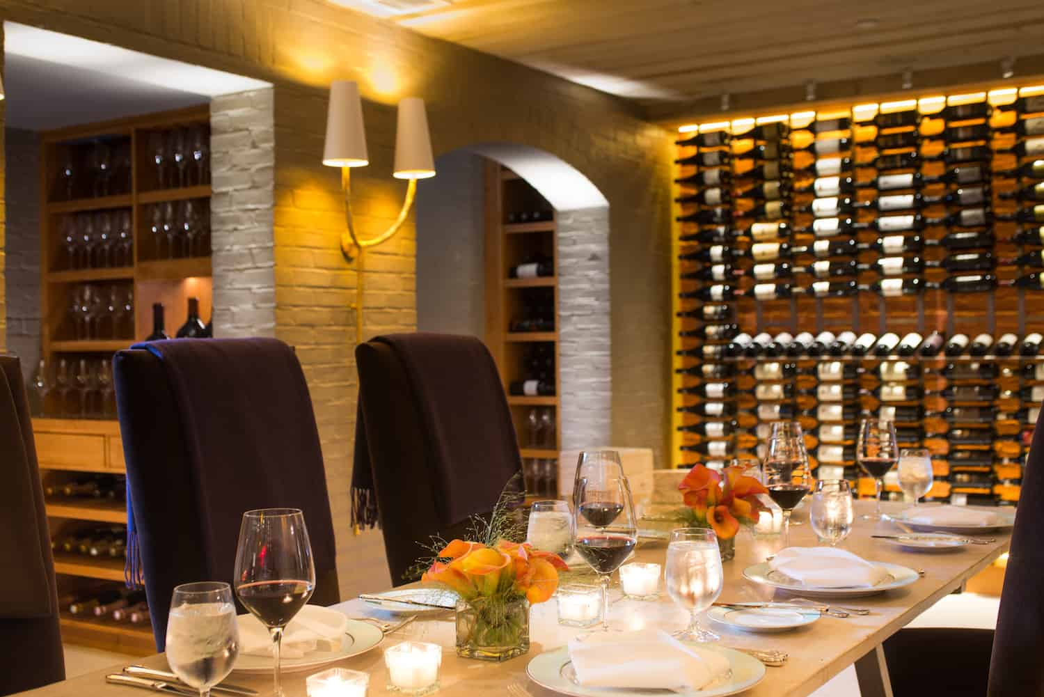 A set table inside the wine cellar dining area of Magdalena inside The Ivy Baltimore.