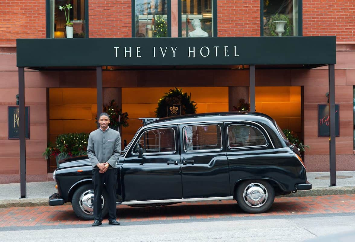 Chauffeur standing in front of the old-fashioned London Cab. He is waiting just outside of The Ivy Baltimore, ready to take you where you want to go.
