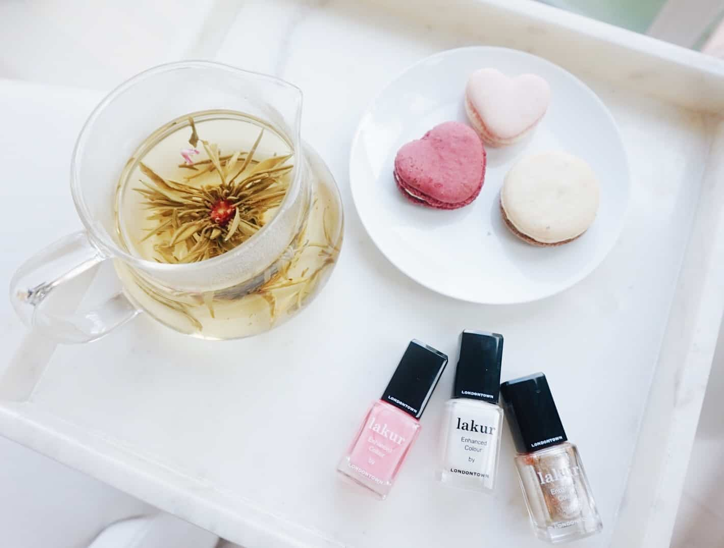 heart cookies on a plate, next to three bottles of nail polish. Enjoy tea while at The Ivy Spa.