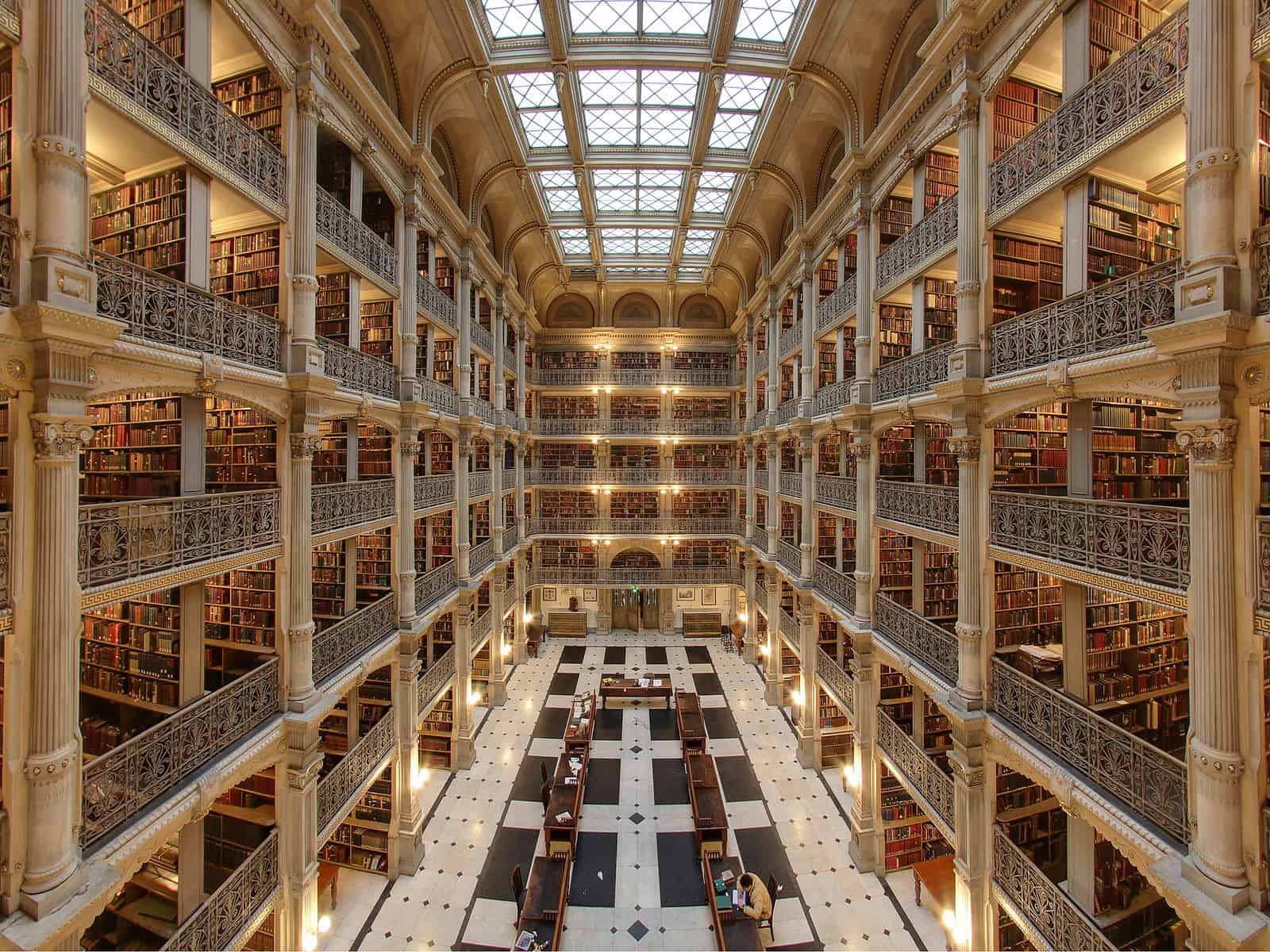 Photo from the second floor of George Peabody Library. Reading desks can be seen on the ground floor and a skylight lights the railings of the floors above.