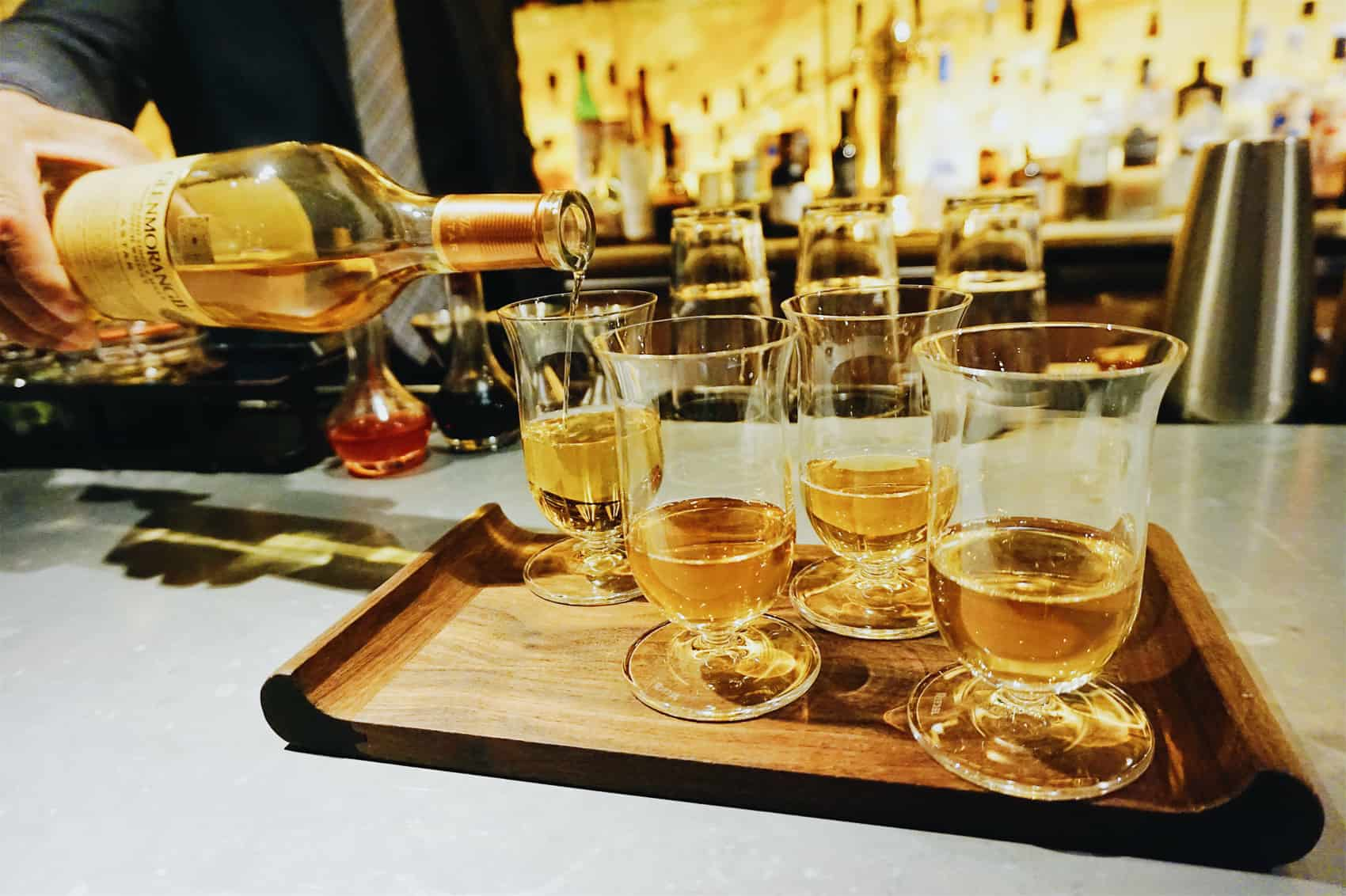 Bartender pouring a fourth glass of whiskey inside the Ivy Baltimore. These drinks are prepared for guests, resting on a serving tray.