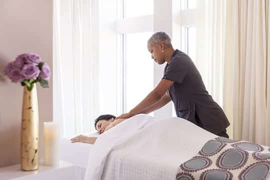 A massuese working with an Ivy Hotel guest. The guest remains relaxed in this well lit room.