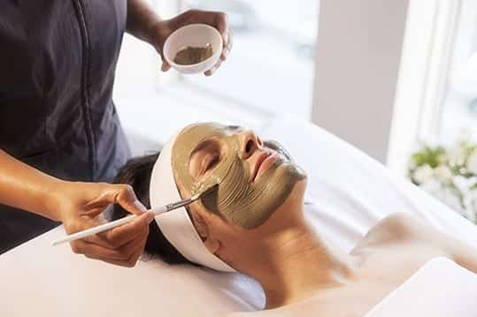 An Ivy Hotel Spa employee paints a mask upon a guest wrapped in towels on a spa table. Bathed in warm light, the woman smiles.