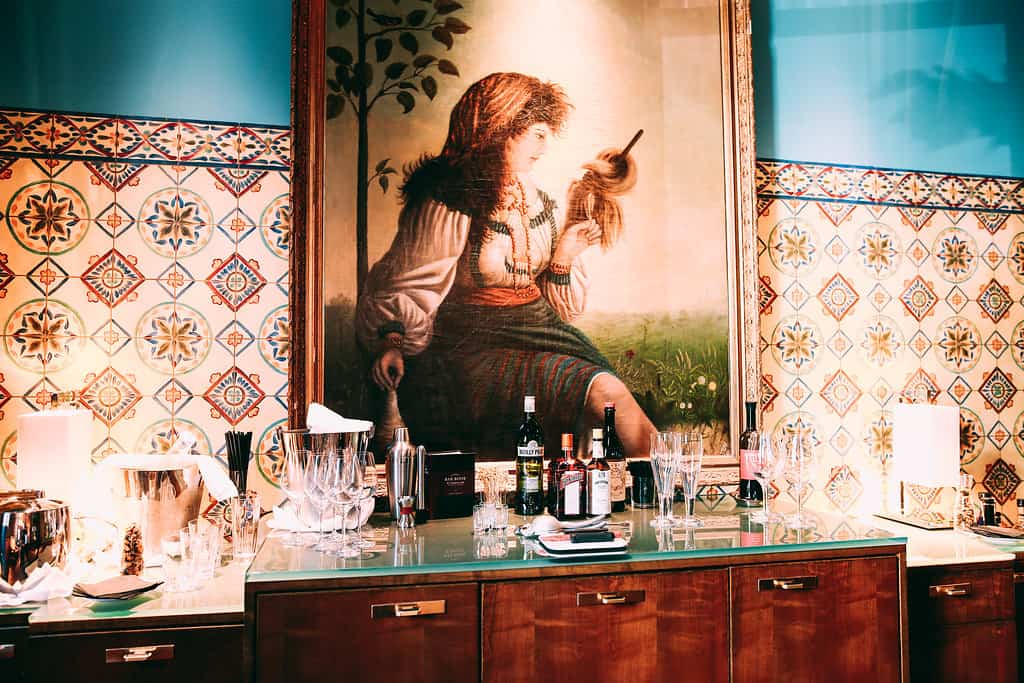 An offering of cocktails, with a set up at the Mansion Bar. Beneath the oil painting, a paneled cabinet can hold all the components to mix up something great.