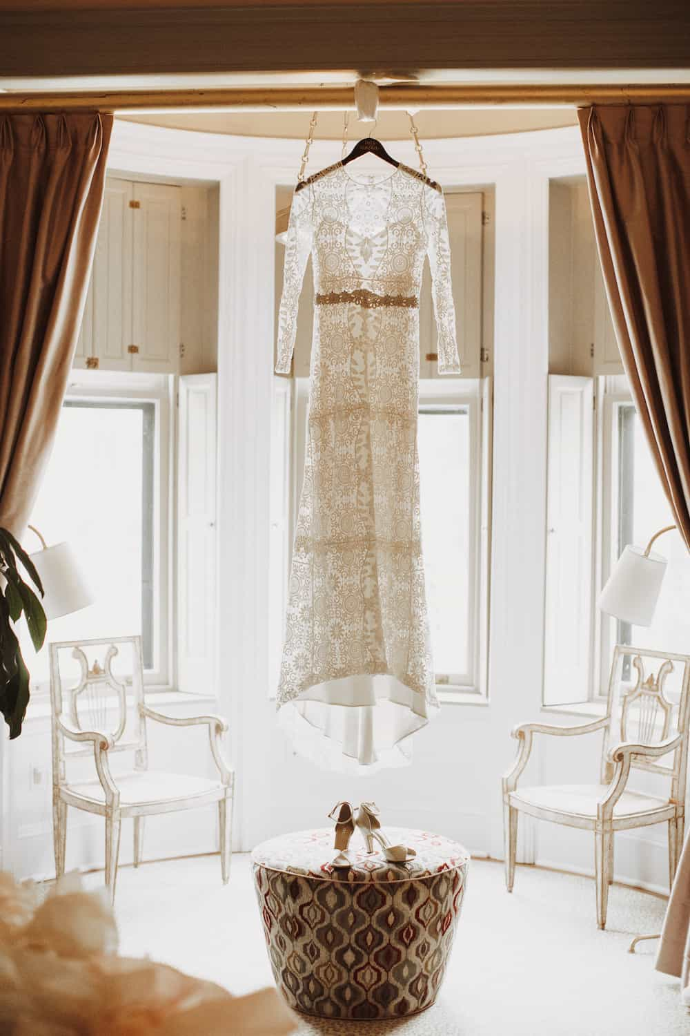Wedding dress hangs in the lit bridal space. Photography from The Ivy Baltimore.