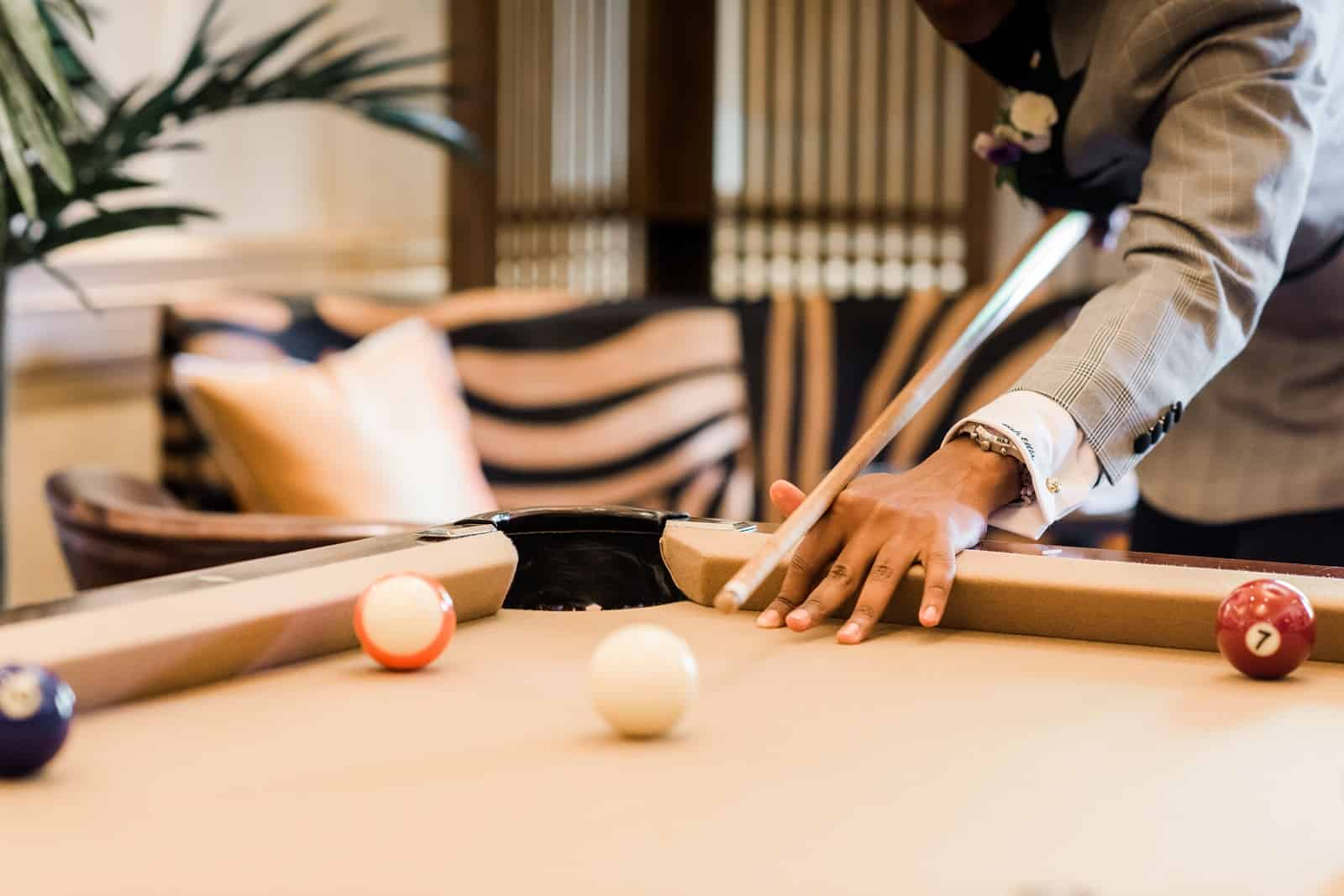 Closeup of a guest playing pool in an entertainment area of The Ivy Baltimore.