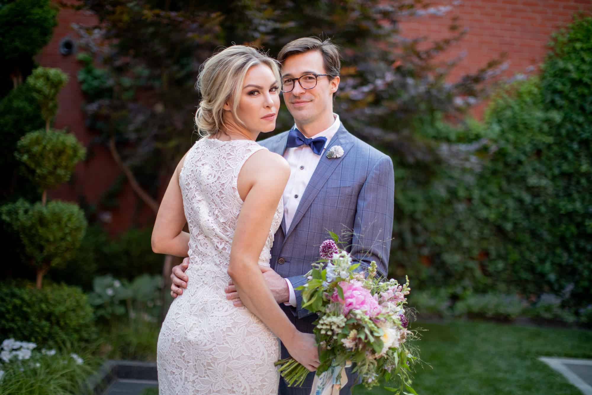 Groom and bride with bouquet standing in ivy courtyard